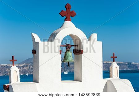 White bell tower with red cross in Santorini - Greece