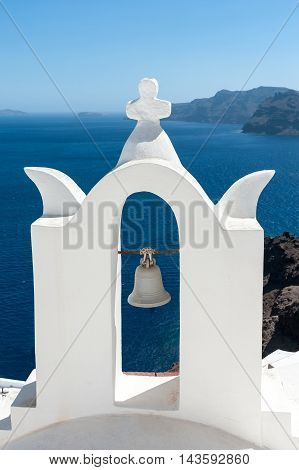 White bell tower in front of Santorini island - Greece