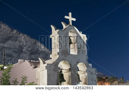 White bell tower at night in Santorini - Greece