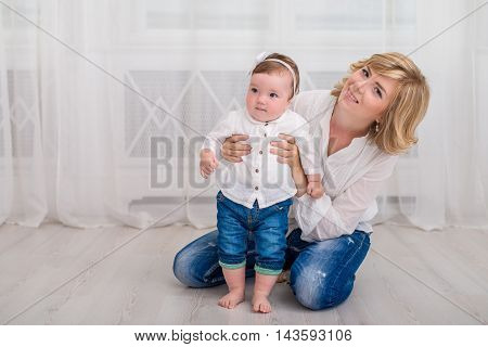 Young mother play at home with her little daughter. Mom and daughter dressed in white shirt and jeans