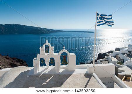 Top of orthodox church with greece flag in Santorini - Greece