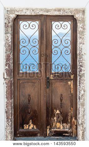 Grunge old door in front of the sea in Santorini