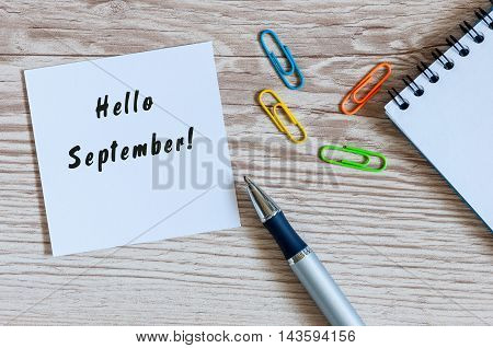 Hello September wrote at paper sticker on wooden workplace background.