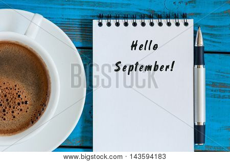 Hello September wrote at paper notepad on blue wooden background with cup of morning coffee. Top view.