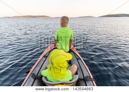 Brothers on a new adventure with father on a kayaking trip to a near by island to sleep under the stars. Concept photo of a family quality time father and sons bond.