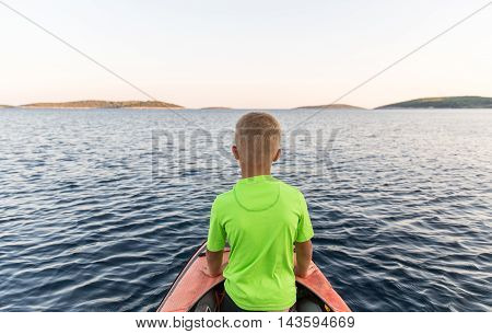 Young bou on an adventure with father taking a kayaking trip to a near by island to sleep under the stars. Concept photo of a family quality time father and sons bond.