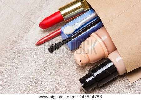 Makeup products buying theme. Paper shopping bag full of various makeup cosmetics and accessories lying on on shabby wooden surface