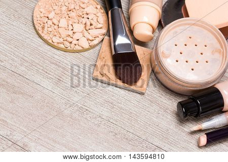 Beauty theme background. Various makeup products and accessories to even out skin tone and complexion. Concealers, foundation, powder, brushes, sponges on shabby wooden surface. Copy space