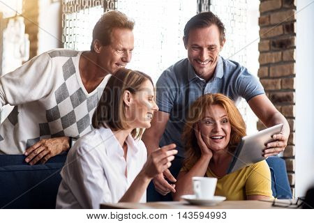 Nice talk. Cheerful and positive group of people using tablet while being indoors