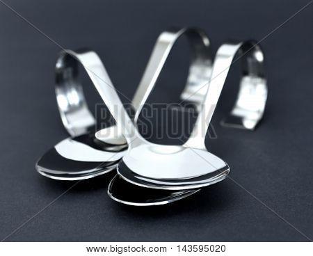 Elegant silver spoons, studio shot on black background.