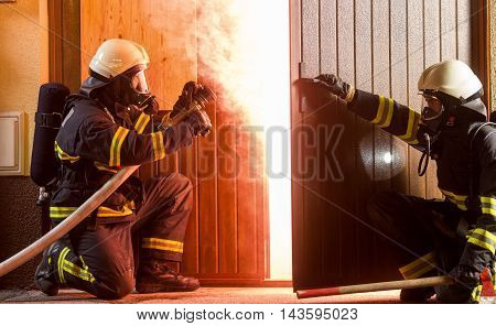 Firefighters ready to enter a blazing room.