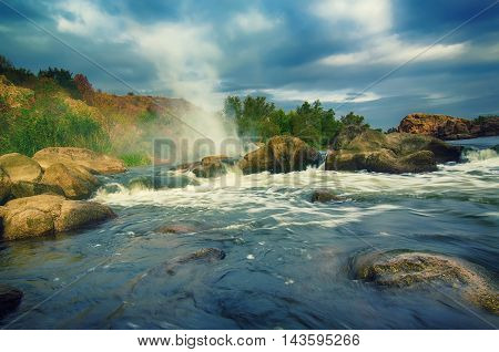 Mountain fast flowing river stream of water in the rocks with dark blue sky and fog