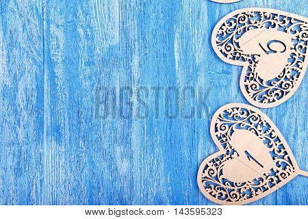 wooden figures in the form of hearts carved on a blue wooden background