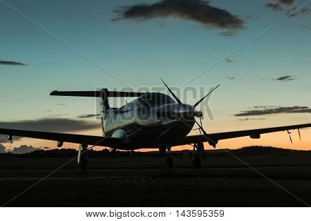 Single-engined business airplane on runway after sunset