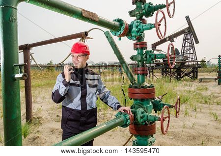 Oilfield worker near wellhead valve wearing red helmet and work clothes talking on the radio. Pump jack background. Oil and gas concept.