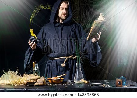 Halloween. The Medieval Alchemist Conducts Holding A Skull With Candle Reading A Book At The Table I