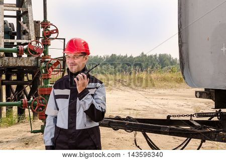 Worker talking on the radio near pump jack wellhead and tank trailer in the oilfield. Oil and gas concept.