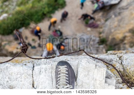 Shoe on the top of rock at climbers background