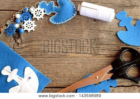 Felt anchor keychain, scissors, white thread, pin, paper pattern, blue felt piece on old wooden background with empty place for text. Needlework and sewing crafts concept. Summer background