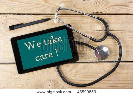 We take care - Workplace of a doctor. Tablet, medical stethoscope, black pen on wooden desk background. Top view.