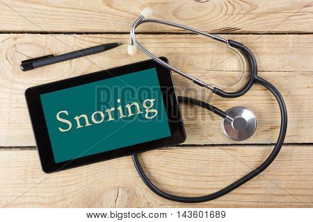 Snoring - Workplace of a doctor. Tablet, medical stethoscope, black pen on wooden desk background. Top view.