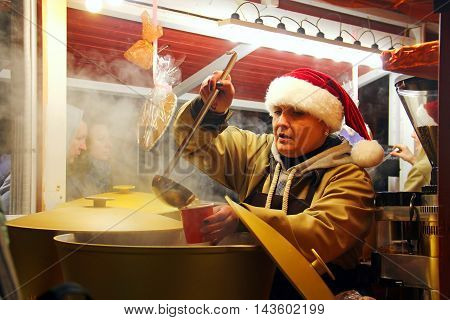 KYIV, UKRAINE - DECEMBER 20, 2015: Woman sell mulled wine at traditional Christmas market on Sophia Square in Kyiv