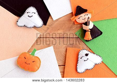 Halloween cute felt crafts. Homemade small witch with broom, pumpkin head, two ghosts. Halloween home decor, colored felt pieces on wooden background with copy space for text. Autumn background