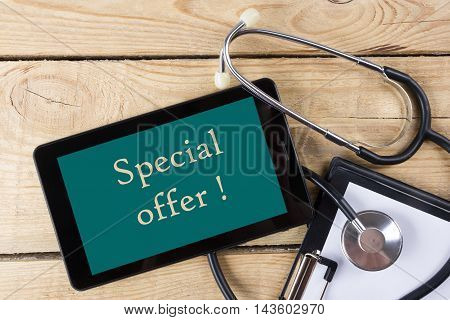 Special offer  - Workplace of a doctor. Tablet, stethoscope, clipboard on wooden desk background. Top view.