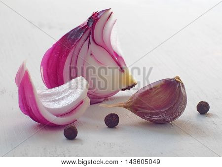 Red onion, garlic and black pepper on wooden table. Selective focus in the front. Macro image.
