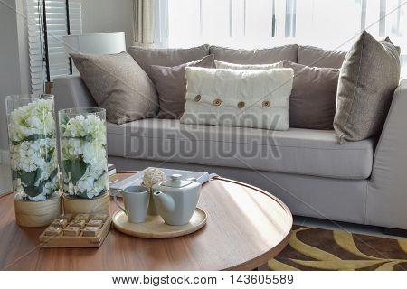 Decorative Tea Set And Glass Vase On Wooden Round Table In Living Room Interior