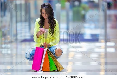 Portrait of the attractive smiling brunette in shopping mall with a bags mobile phone credit card in a hand.