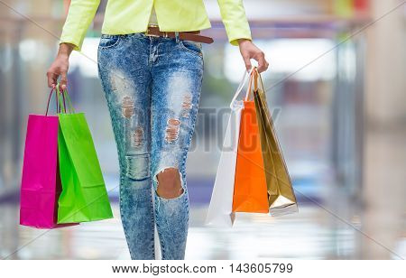 Portrait of the attractive smiling brunette in shopping mall with a bags credit card in a hand.