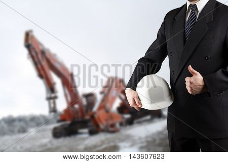Close up of engineer hand holding white safety helmet for workers security standing in front of  blurred construction site in background