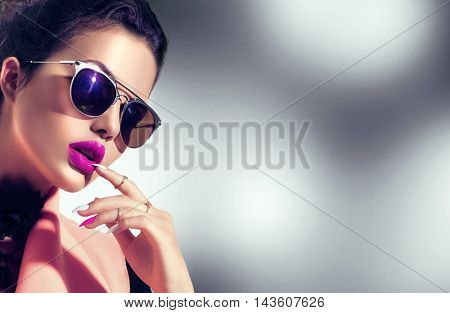 Beauty Fashion model girl with brown hair wearing stylish sunglasses. Sexy woman portrait with perfect makeup and manicure, trendy accessories and fashion wear. Beauty trends