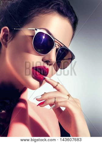 Beauty Fashion model girl wearing stylish sunglasses. Sexy woman portrait with perfect makeup and manicure, trendy accessories and fashion wear. Beauty trends