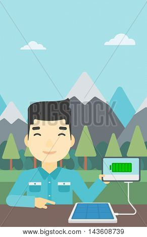 An asian man charging tablet computer with solar panel on the background of mountains. Charging digital tablet from portable solar panel. Vector flat design illustration. Vertical layout.