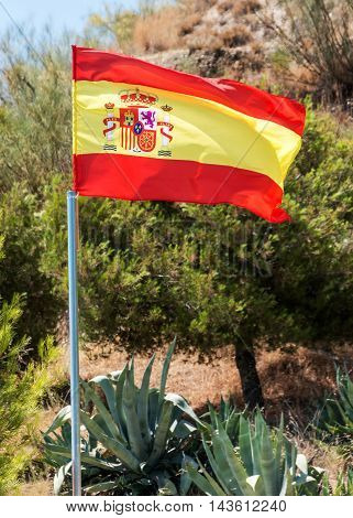Spanish flag on a pole flying against authentic Spanish countryside focus on flag. shot outdoors in inland Granada Andalusia