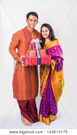 indian young Couple in traditional clothing standing with gift boxes, isolated over white background