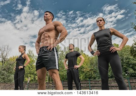 Fitness instructor posing with his team, low angle view