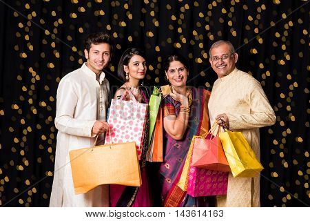 indian family with shopping bags standing isolated over black background on diwali