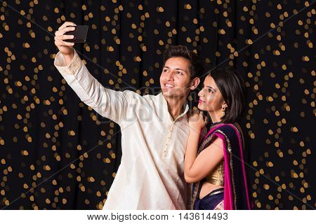 indian young Couple taking a self portrait or selfie using smart-phone in diwali festival