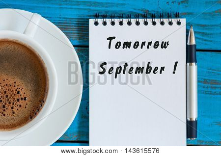 September tomorrow word wrote on white notepad on blue wood background with cup of morning coffee. Back to school time..