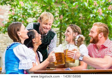 ive friends in Bavarian clothes clinking beer glasses in beer garden
