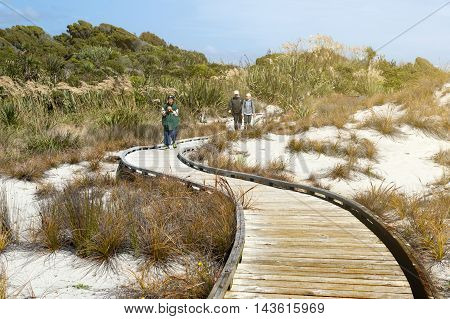 Haast New Zealand - February 2016 : Tourists walking on wooden walkway by the beach at Tauparikaka Marine Reserve Haast New Zealand