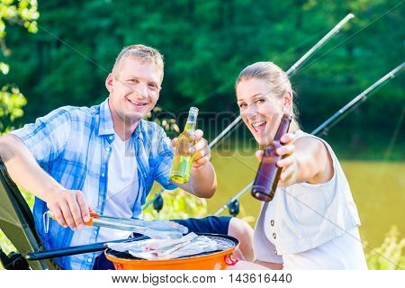 Couple of woman and man drinking beer and having bbq after fishing at the lake