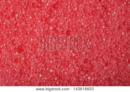 Close-up texture fragment of a red sponge as a backdrop composition