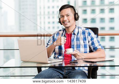 Young asian professional in skyscraper office having coffee and giving the thumbs up sign