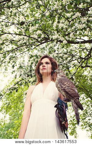 Beautiful Woman with Hawk on Blossom Background