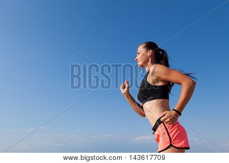 beautiful girl goes in for sports runs and listens to music with headphones