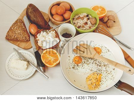 Fried Eggs in the Frying Pan,Breakfast Ingredients.Orange,Bread,Butter,Nuts,Porrige.Kitchen Accessories.Cooking Morning Food.White Table.